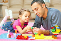 A photo of a young girl and her father on the floor playing with Legos.