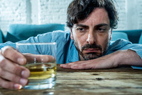 A depressed man looking at a glass of liquor.