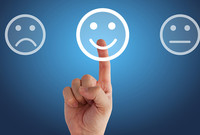 A finger pointing to a happy face icon, with a frowning face and neutral face on either side.