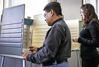 A man and a woman standing at voting booths
