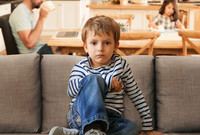 A young boy sitting on a sofa, looking directly into the camera, while his family sits at s table behind him.